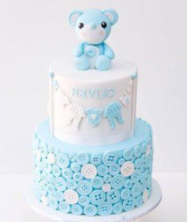 Белый торт с голубыми пуговицами и медведем