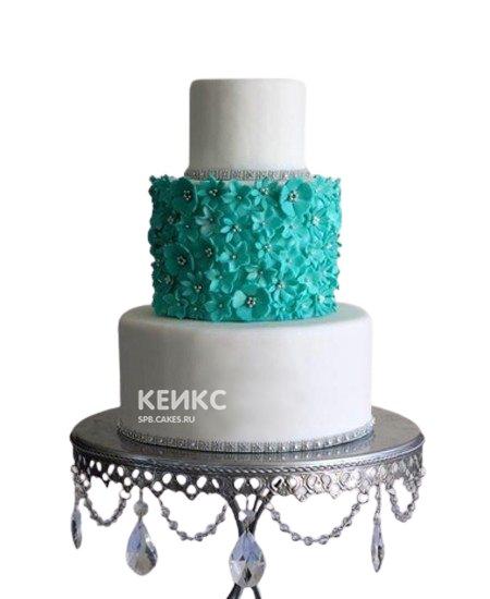 Белый свадебный торт украшенный бирюзовыми цветами