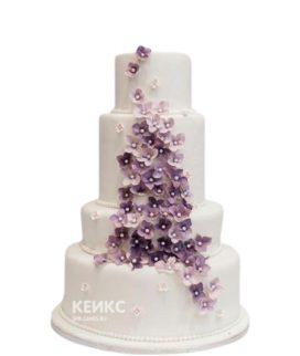 Высокий белый свадебный торт с водопадом фиолетовых цветов