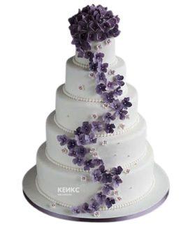 Высокий белый свадебный торт украшенный фиолетовыми цветами