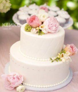 Маленький белый свадебный торт, украшенный живыми пионами