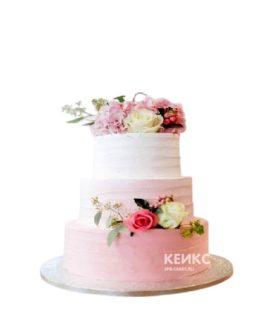 Маленький нежно-розовый свадебный торт с букетами живых цветов