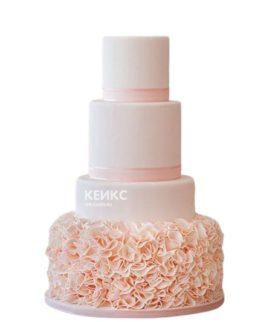 Красивый свадебный торт розового цвета с рюшами на нижнем ярусе