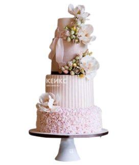 Высокий розовый свадебный торт украшенный цветами и бантом