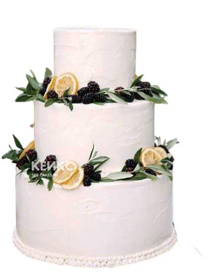 Белый свадебный торт с фруктами украшенный лимонами и ежевикой