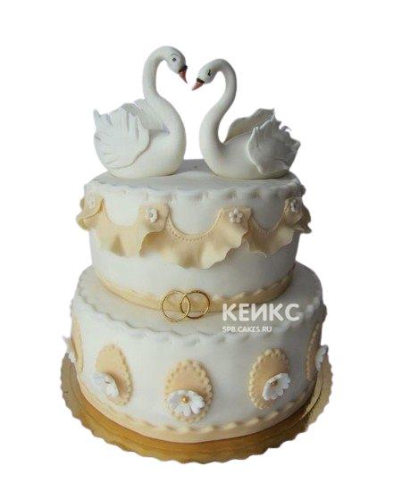 Белый свадебный торт с лебедями и золотыми узорами