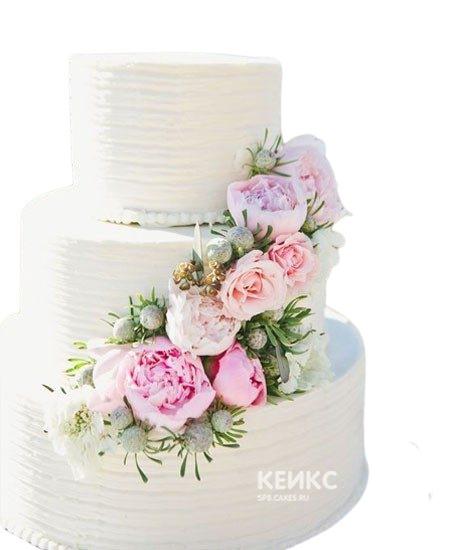 Белый свадебный торт украшенный шикарным букетом живых цветов