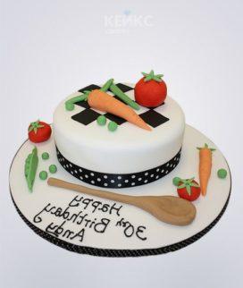 Белый торт с лопаткой и овощами для повара