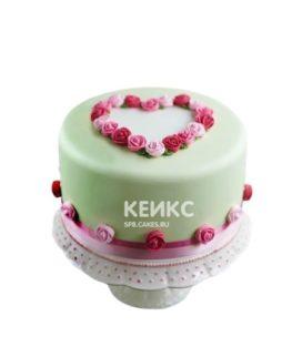 Зеленый торт украшенный розами в форме сердца