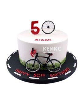 Торт белого цвета с велосипедом и дорогой